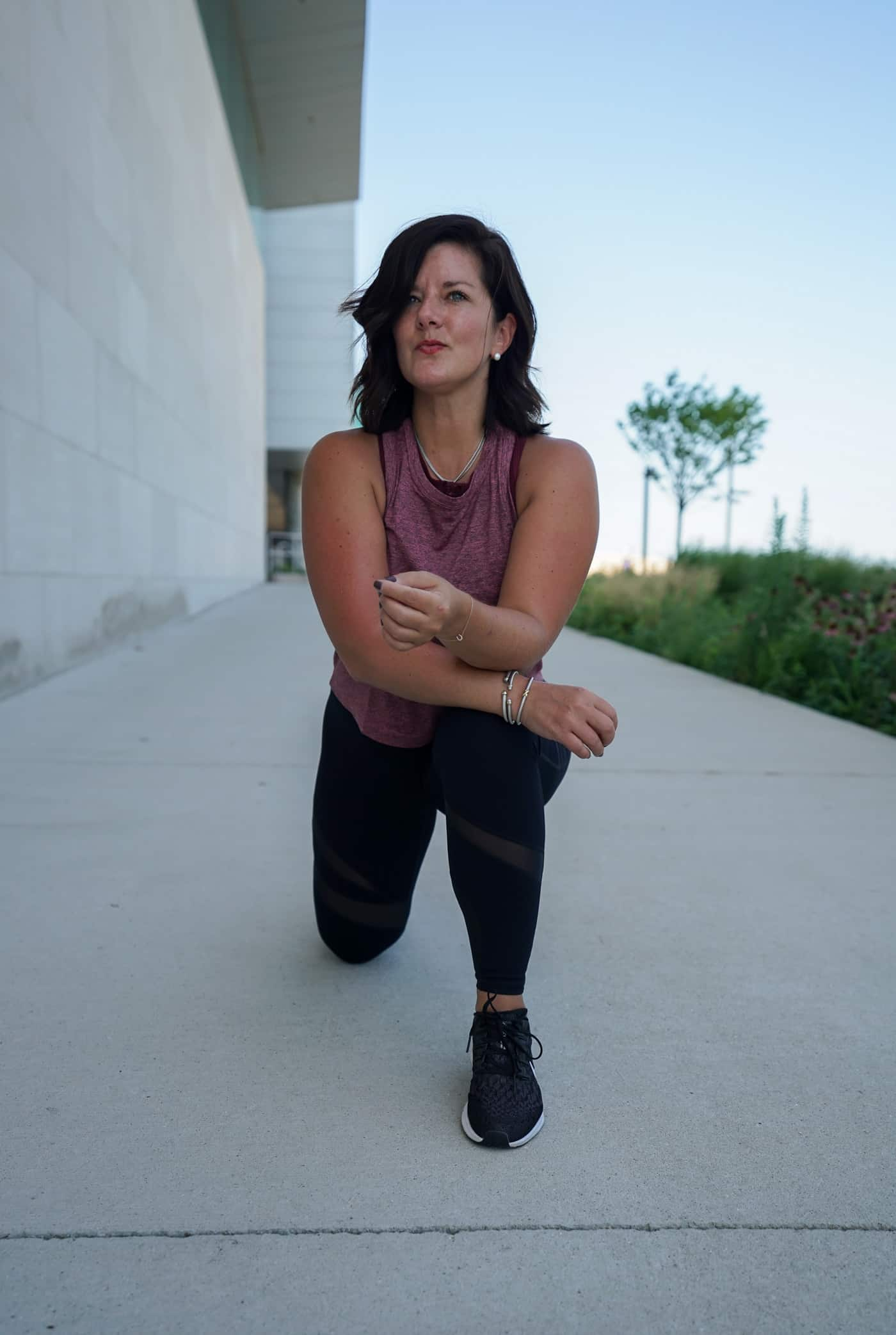 A Lily Love Affair sharing her Fabletics review wearing black leggings, black nike sneakers and a Fabletics sports bra