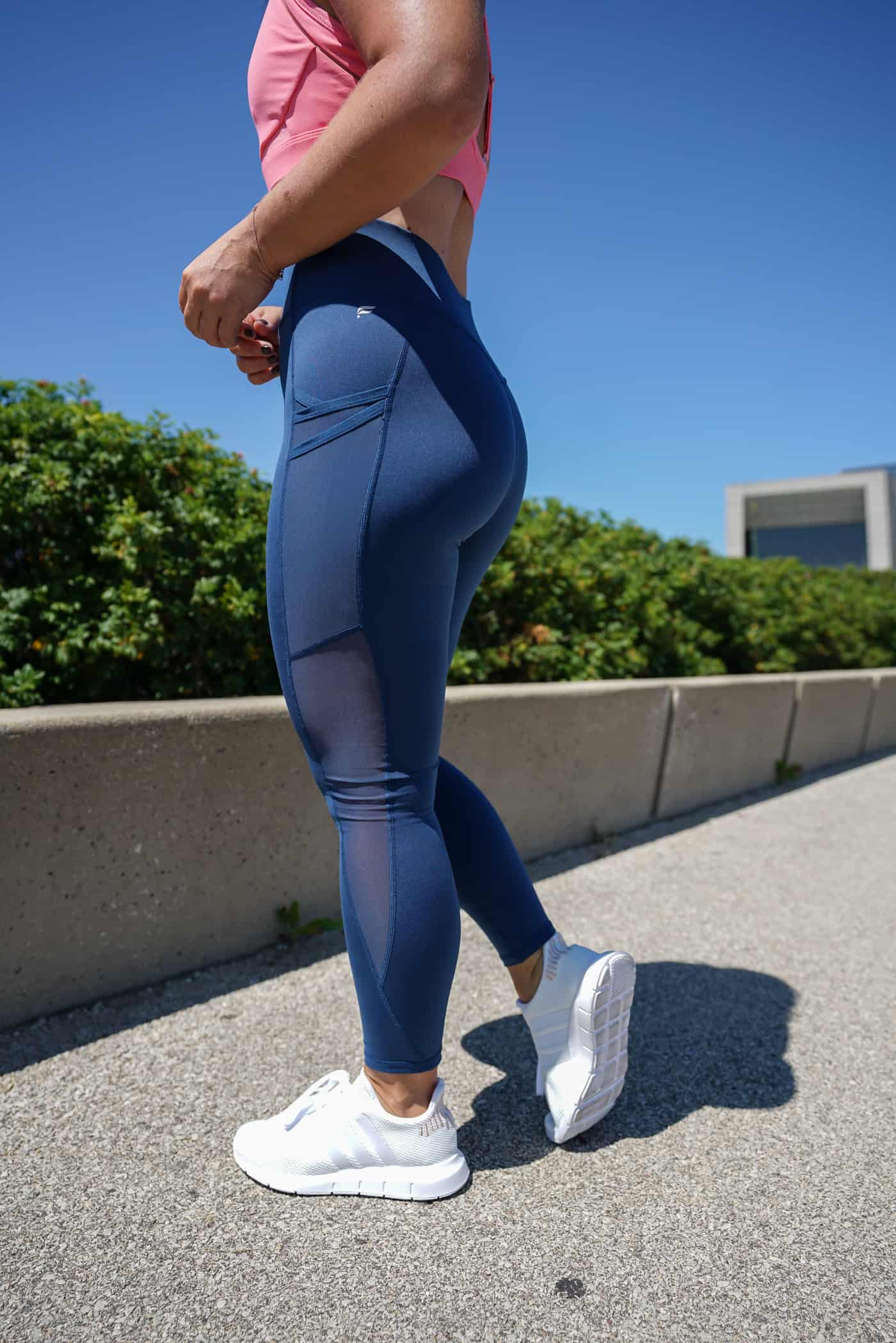 A Lily Love Affair sharing her Fabletics review wearing blue leggings, white adidas sneakers and a Fabletics sports bra