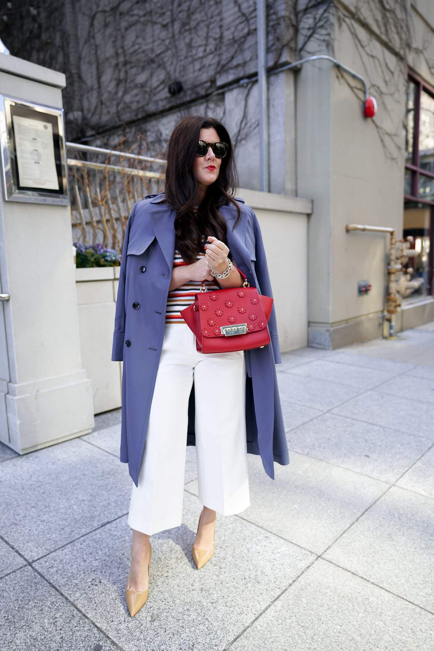 A petite women sharing how to wear a trench coat with white pants and heels