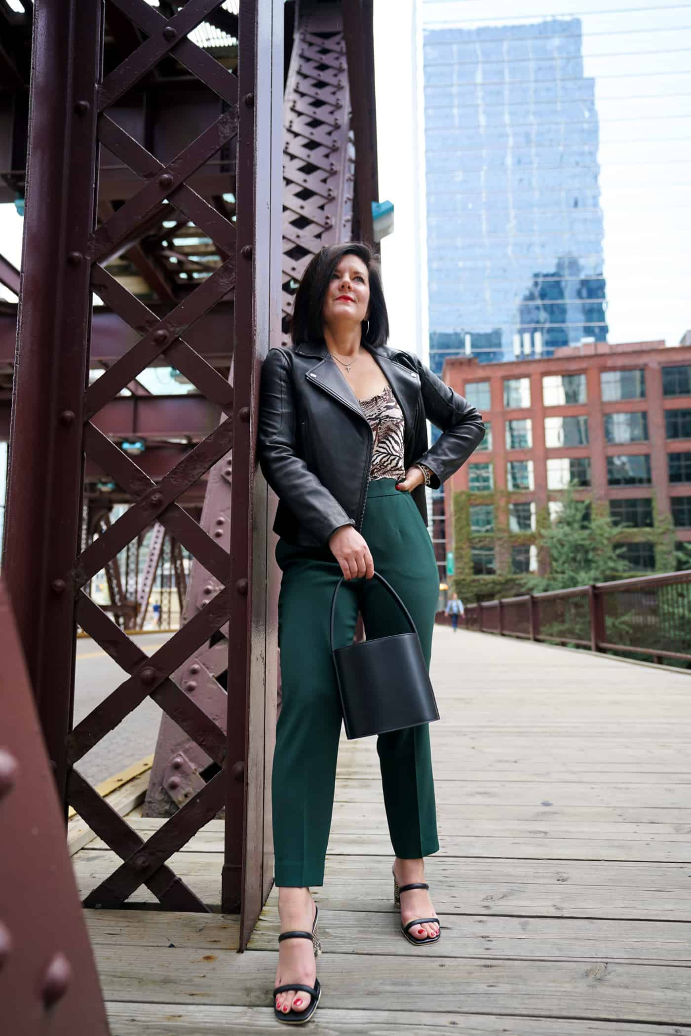 A women wearing green aritzia pants and a black leather jacket