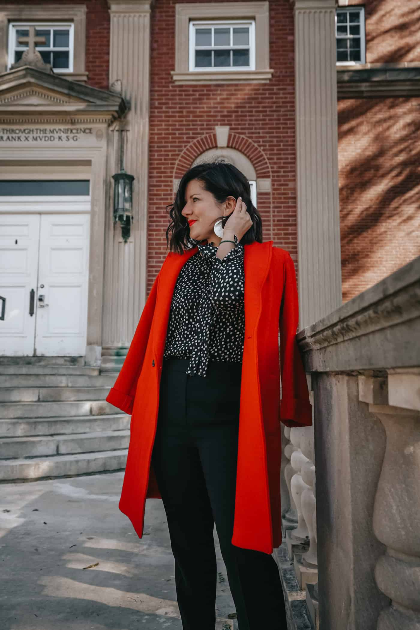 Anna Baun of A Lily Love Affair shares fall fashion under $100 wearing black pants and a red coat