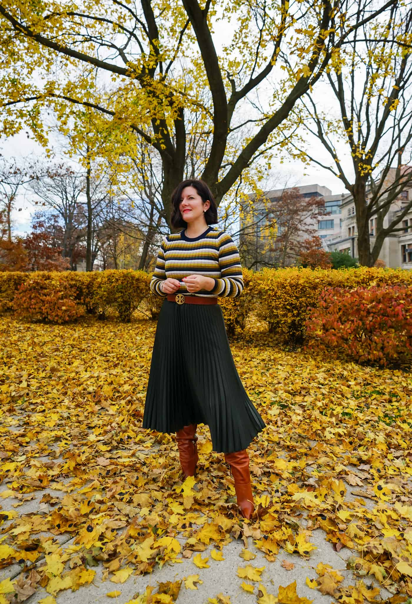 A Lily Love Affair wearing a green pleated skirt, a striped sweater with brown knee high boots