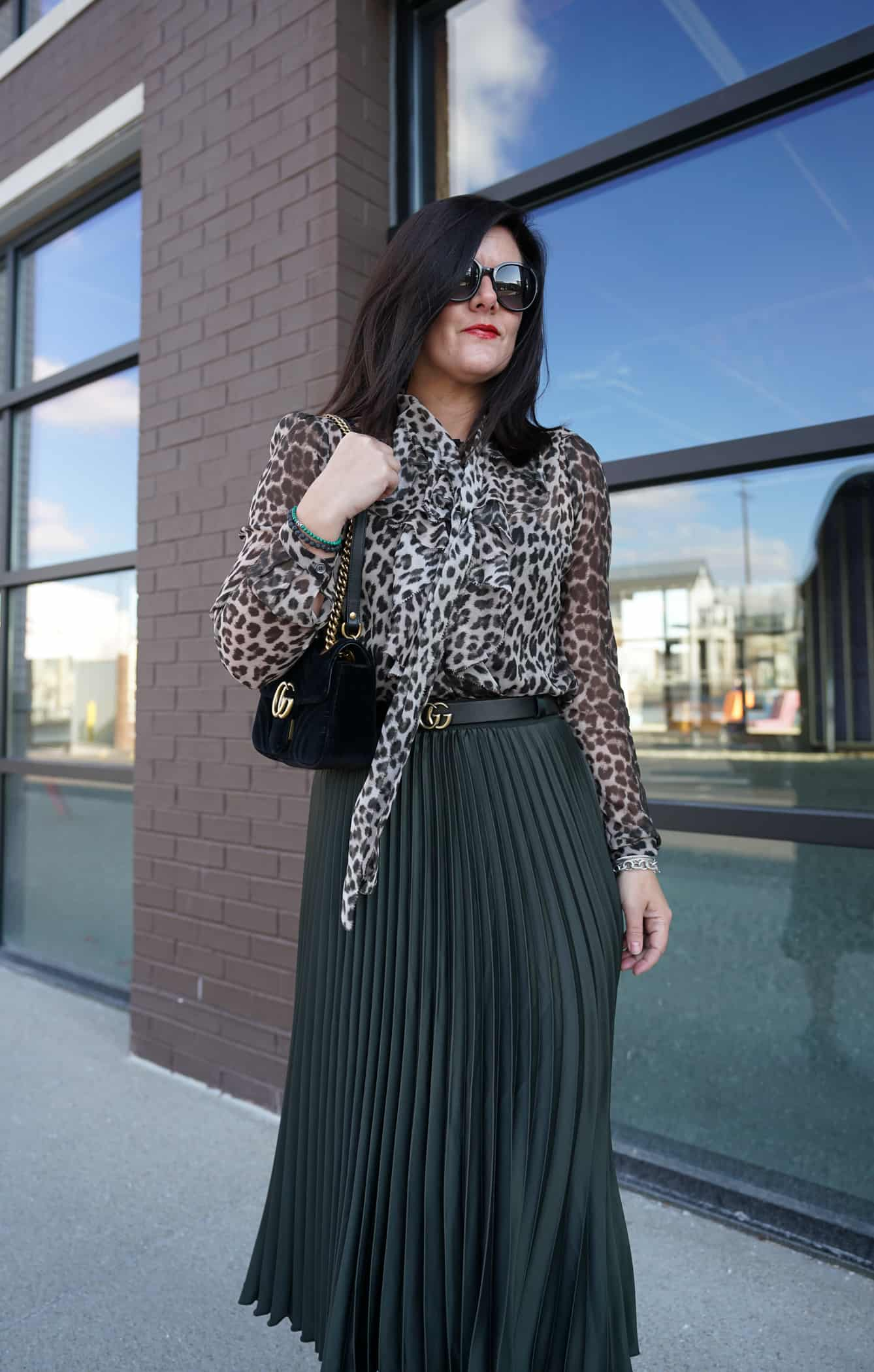 A Lily Love Affair wearing a green pleated skirt, a leopard long sleeve blouse with a black gucci bag
