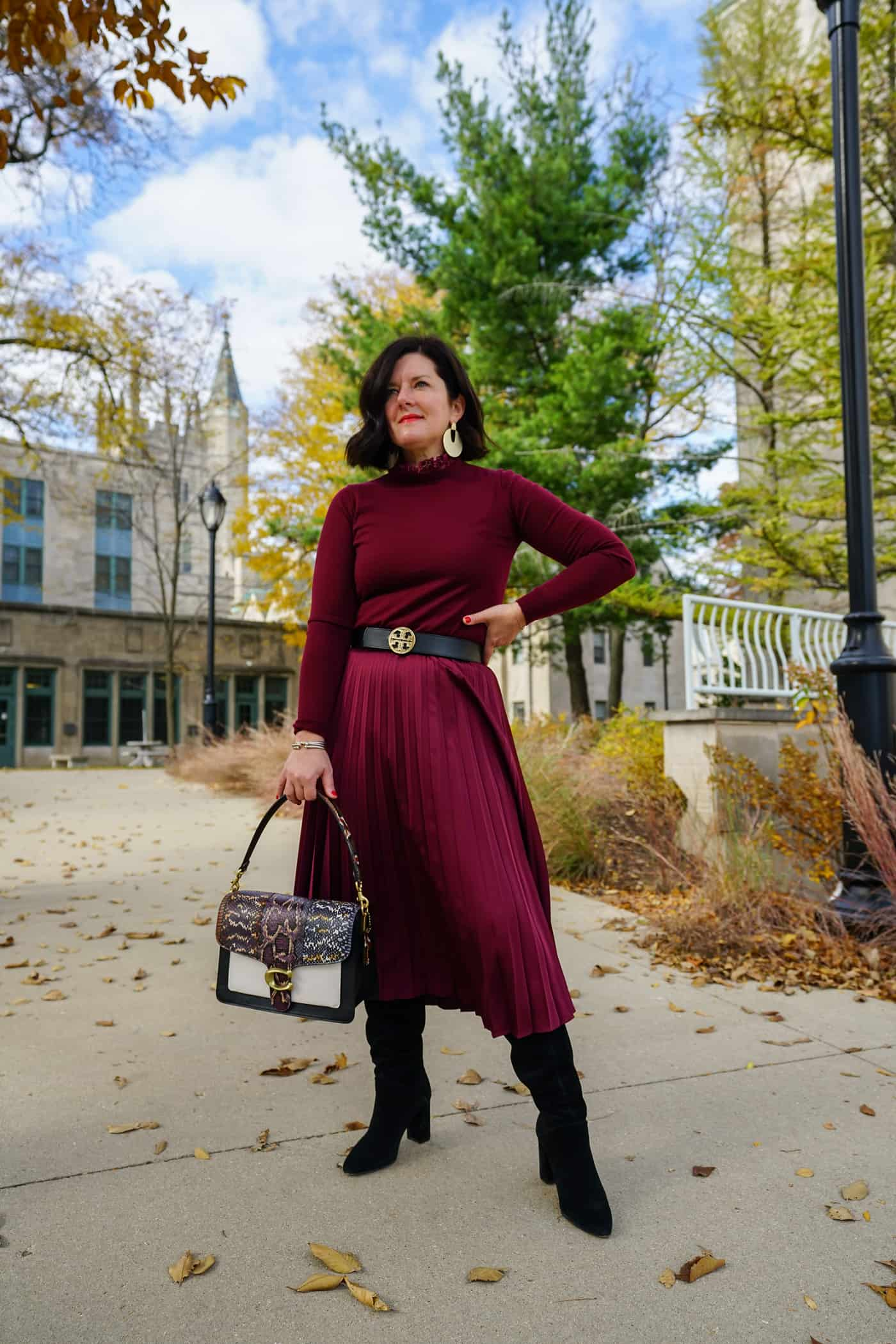A Lily Love Affair wearing a maroon pleated skirt with matching maroon sweater and black knee high boots