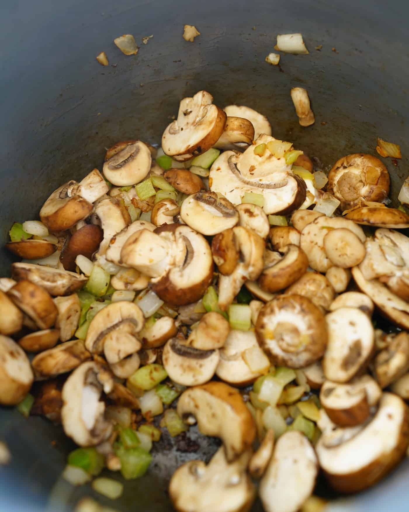 An instant pot filled with mushrooms and onions