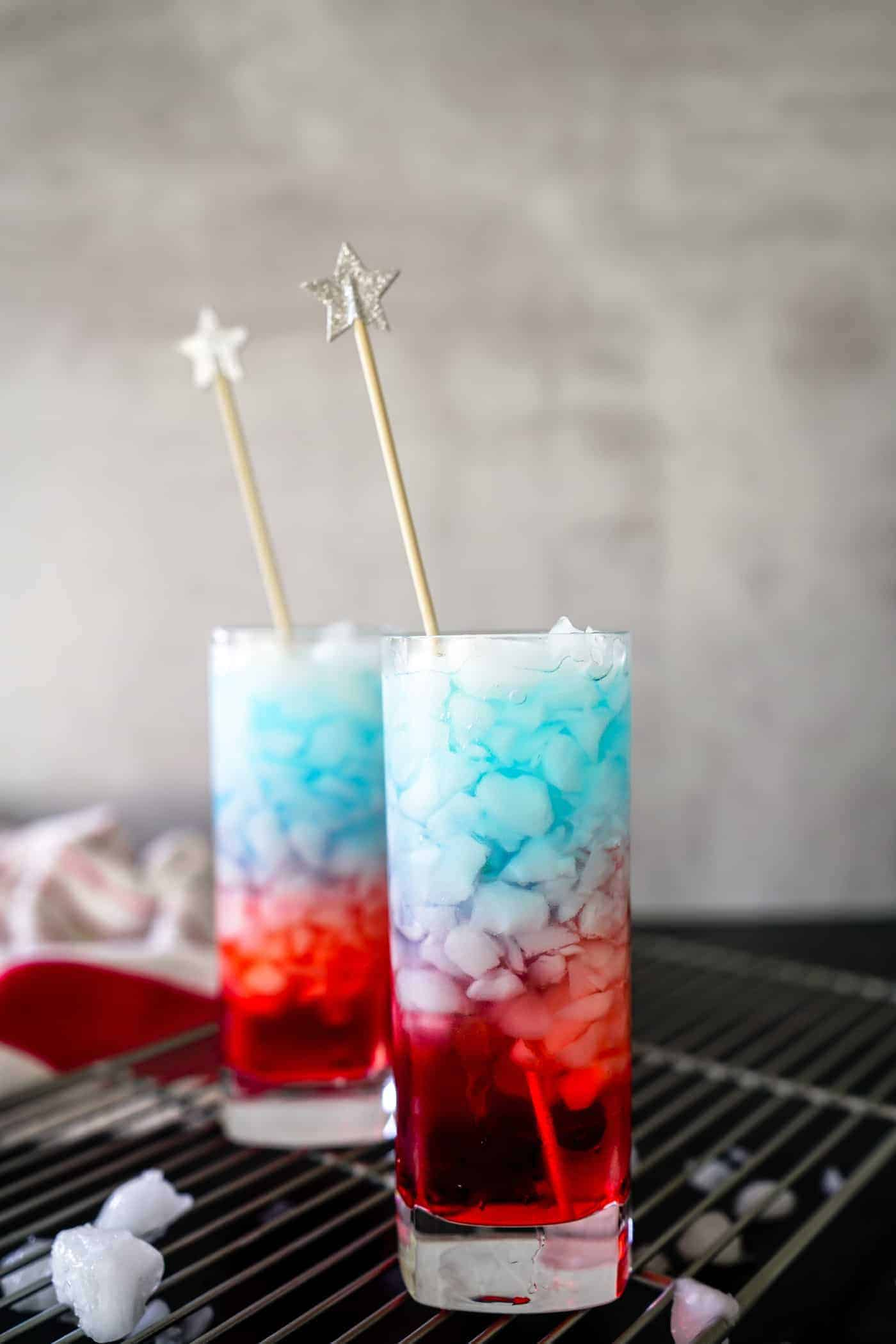 Two tall glasses filled with a red, white and blue bomb pop drink