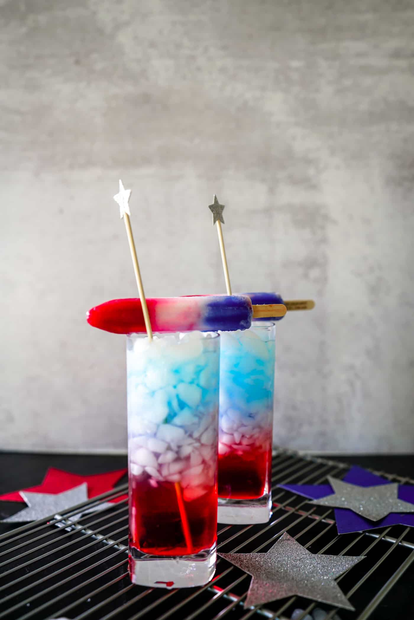 Two tall glasses filled with ice and a bomb pop drink