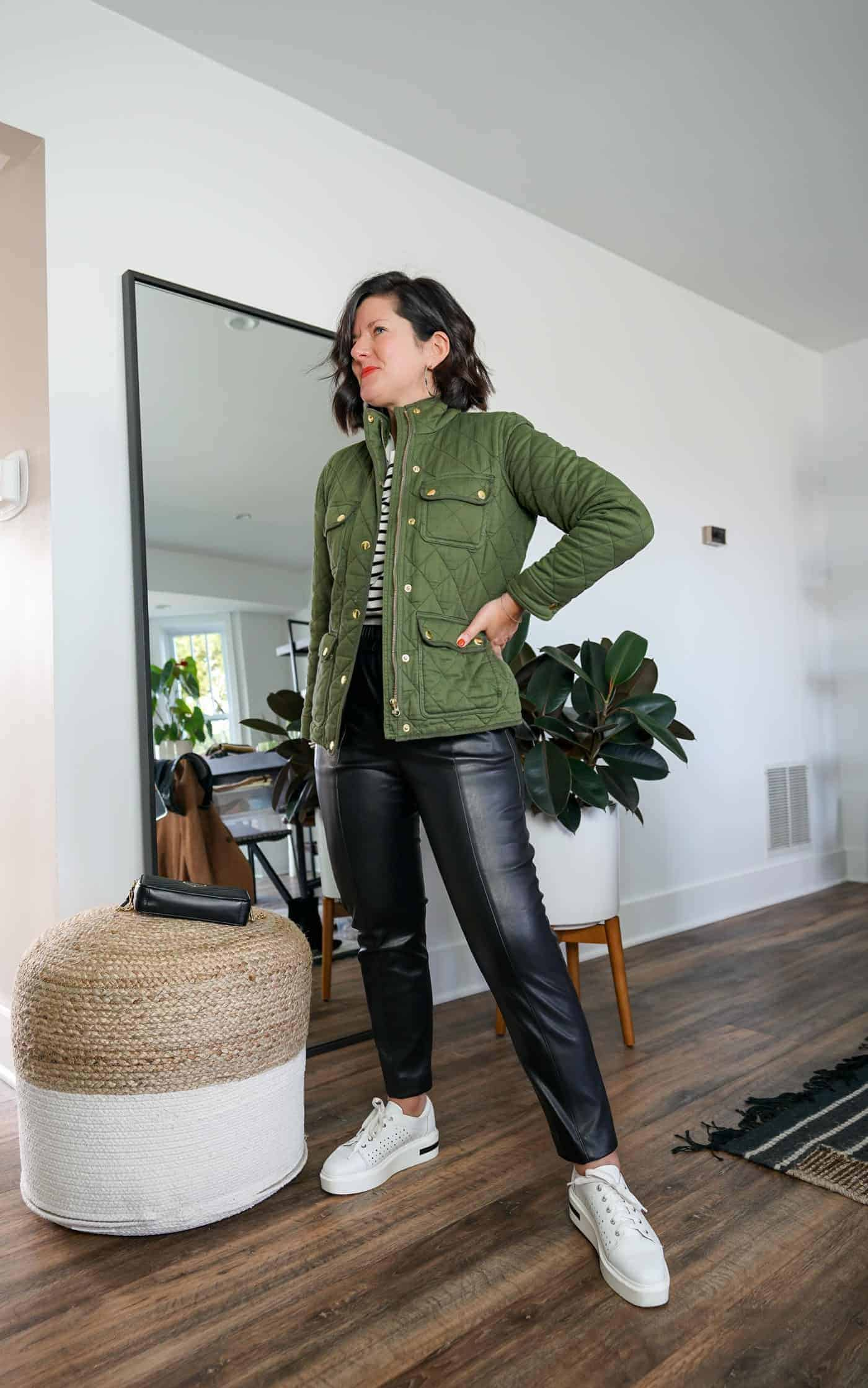 A Lily Love Affair wearing faux leather pants with white sneakers, a striped tee and green jacket