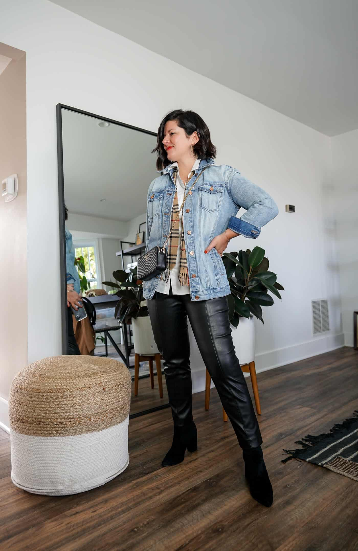 A Lily Love Affair wearing womes faux leather pants with a denim jacket, a white button down blouse and black booties