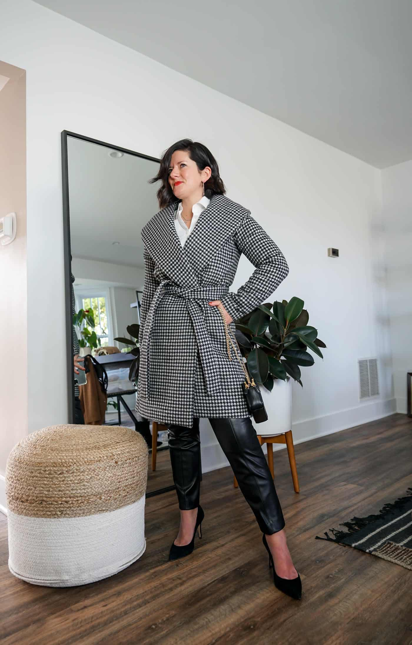 A Lily Love Affair wearing womes faux leather pants with a black and white plaid jacket, a white blouse and black heels
