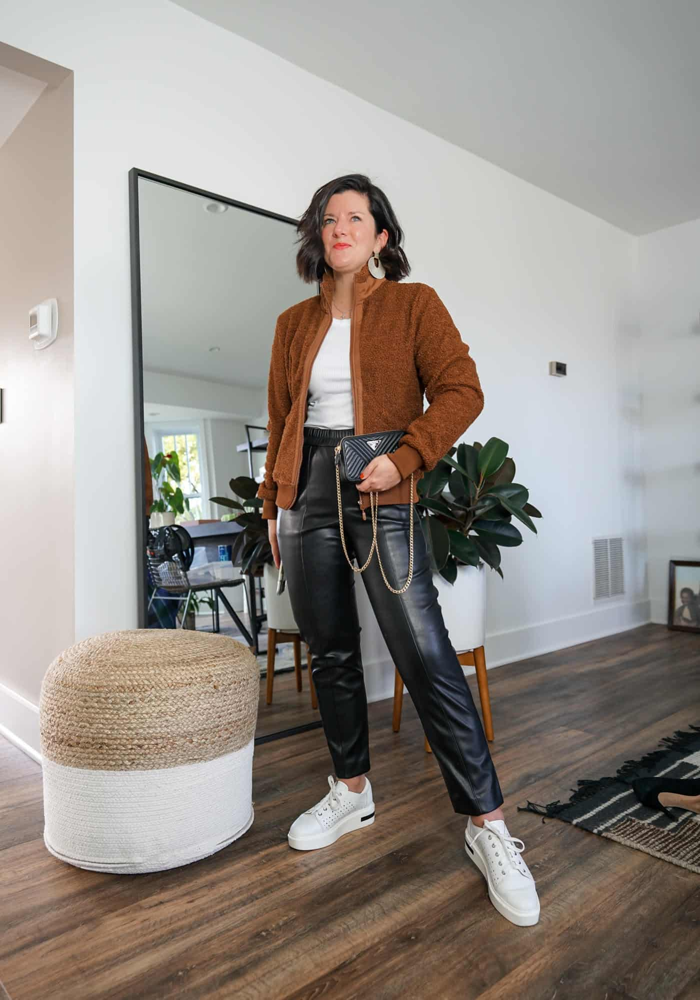 A Lily Love Affair wearing womes faux leather pants with a brown sherpa jacket and white sneakers
