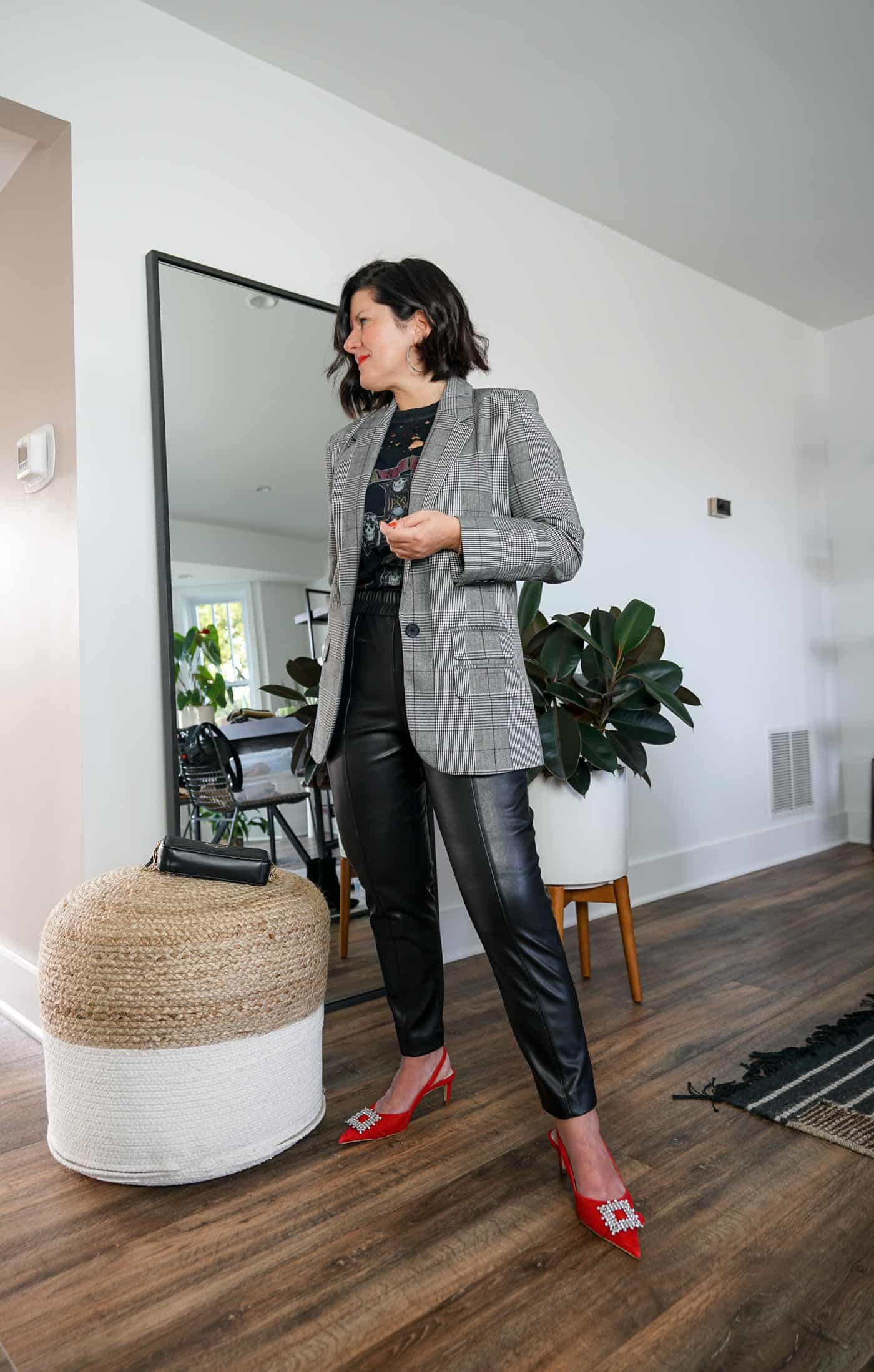 A Lily Love Affair wearing womes faux leather pants with a plaid blazer, a graphic tee and red heels