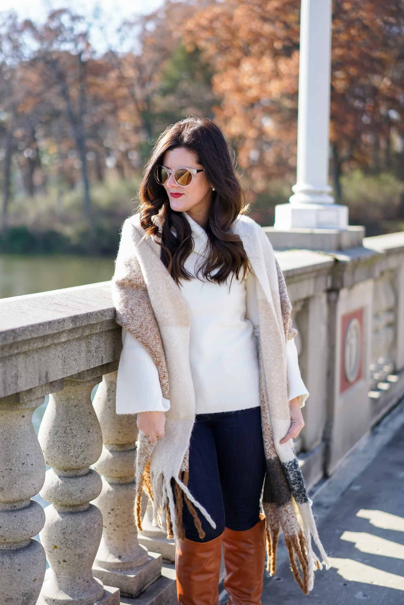 A Lily Love Affair wearing a long plaid scarf, cream turtleneck sweater and tan knee high boots