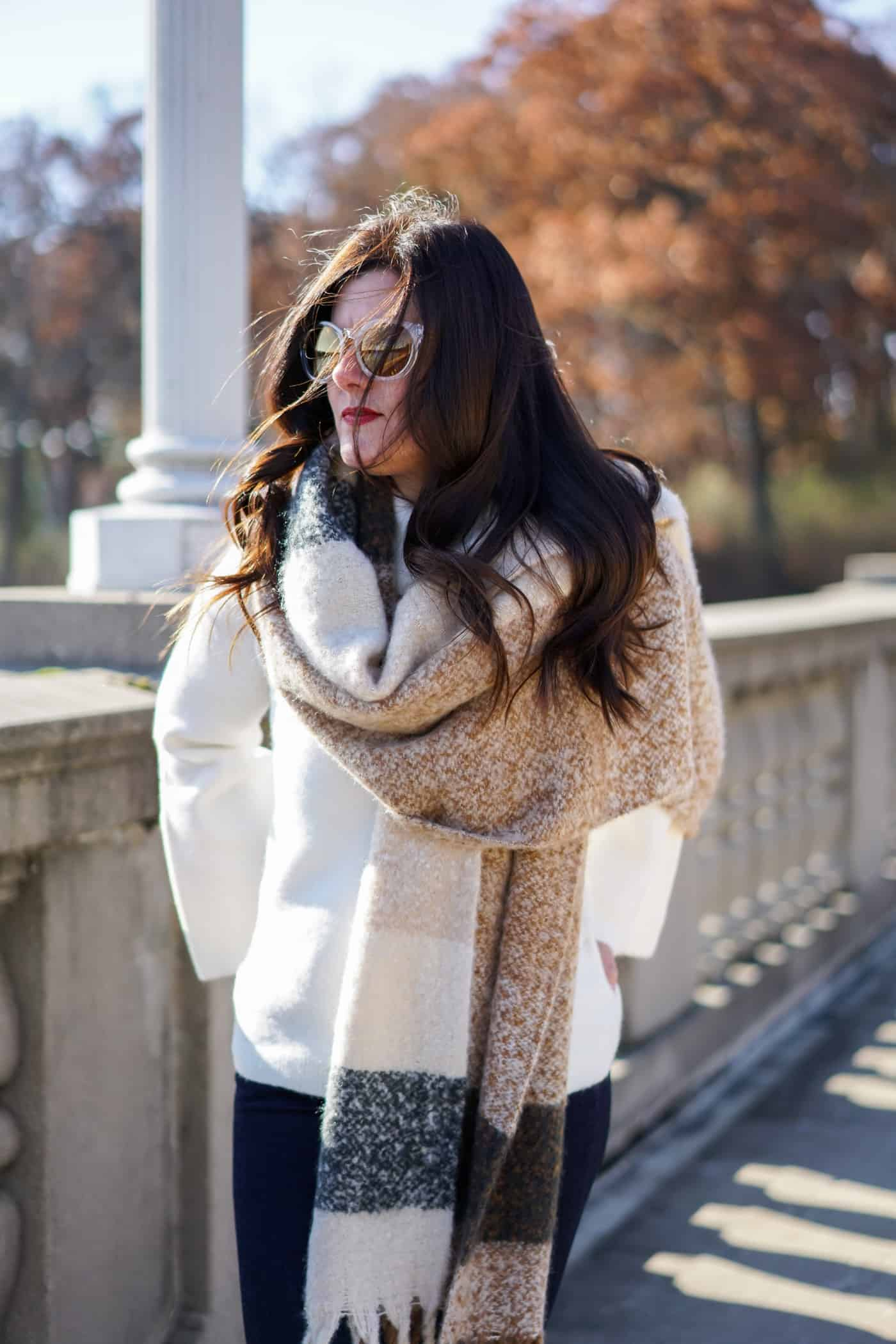A Lily Love Affair shares 30 cute fall sweaters under $30 wearing a long plaid scarf and cream oversized sweater