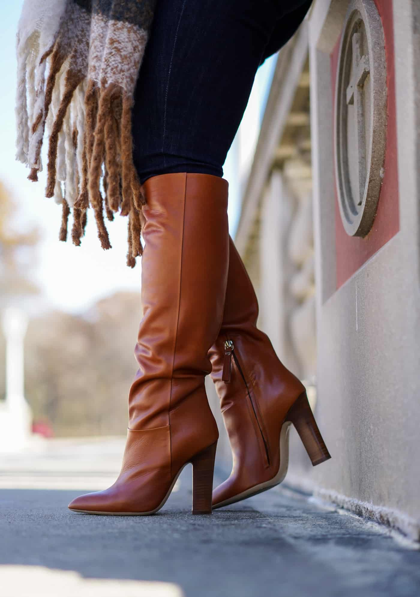 A Lily Love Affair wearing tall brown boots and skinny jeans while sharing 30 cute Fall sweaters
