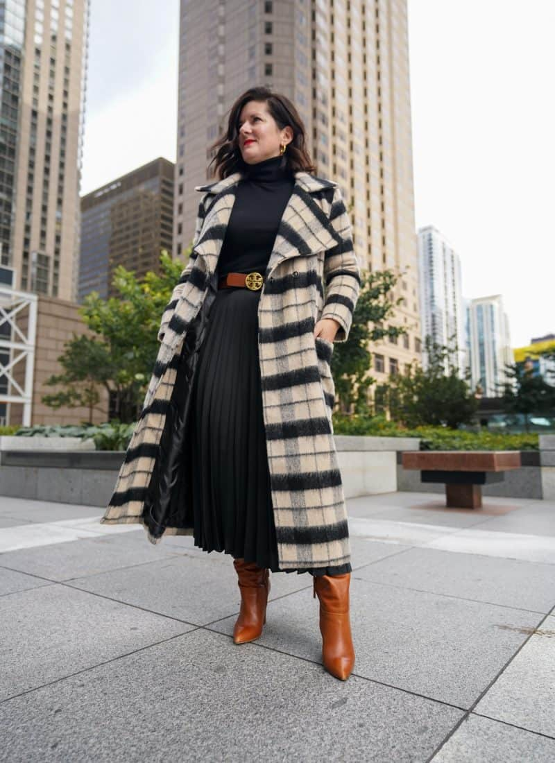 A Lily Love Affair shares how to wear a pleated skirt with black sweater, long plaid coat and brown boots