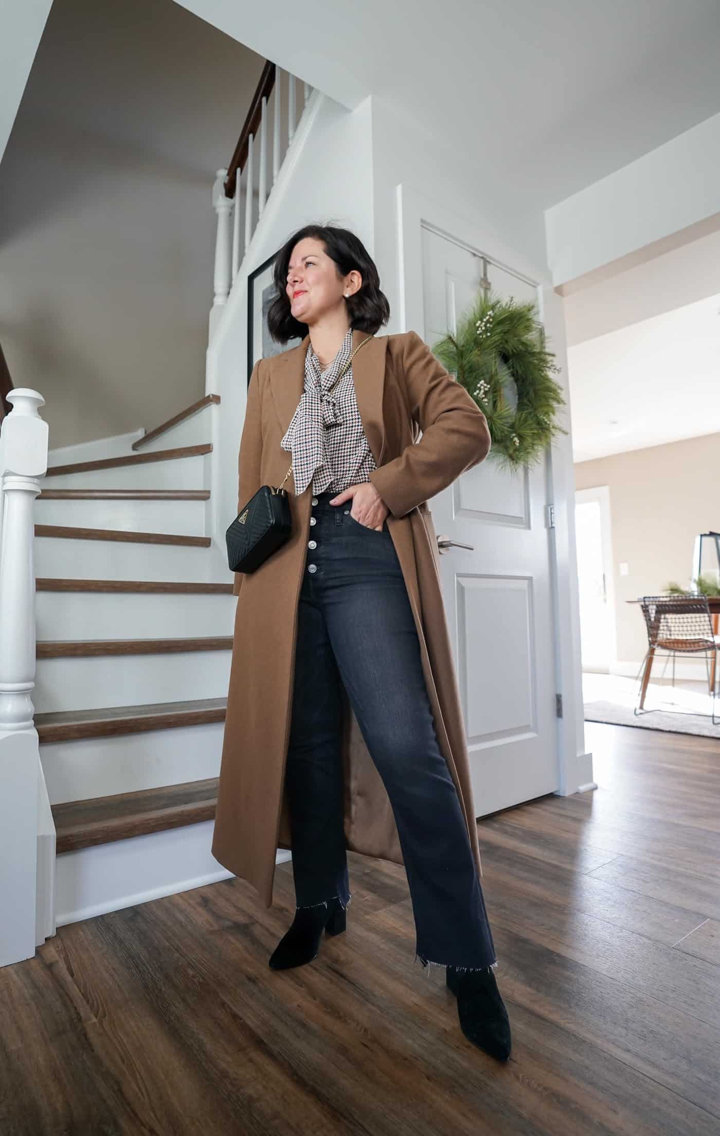 A Lily Love Affair shares a thanksgiving outfit idea wearing a long camel coat, grey flared jeans and a plaid blouse
