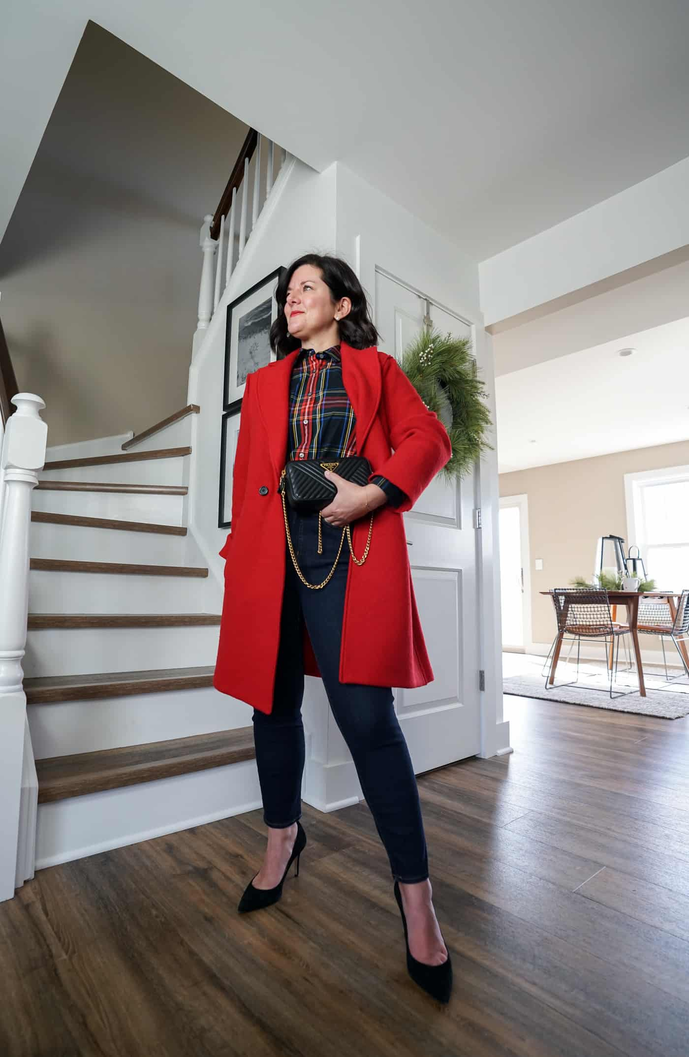 A Lily Love Affair shares a thanksgiving outfit idea wearing a long red coat, a plaid top with blue skinny jeans