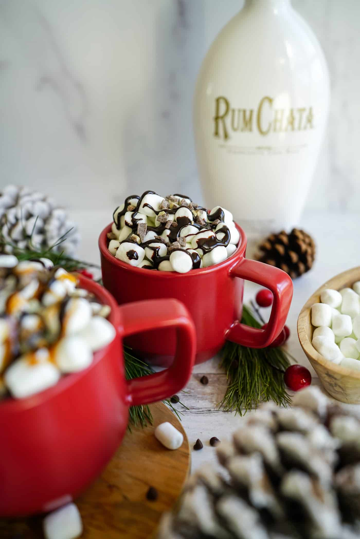 A red coffee mug filled wtih rumchata hot chocolate topped with marshmalloed and chocolate sauce