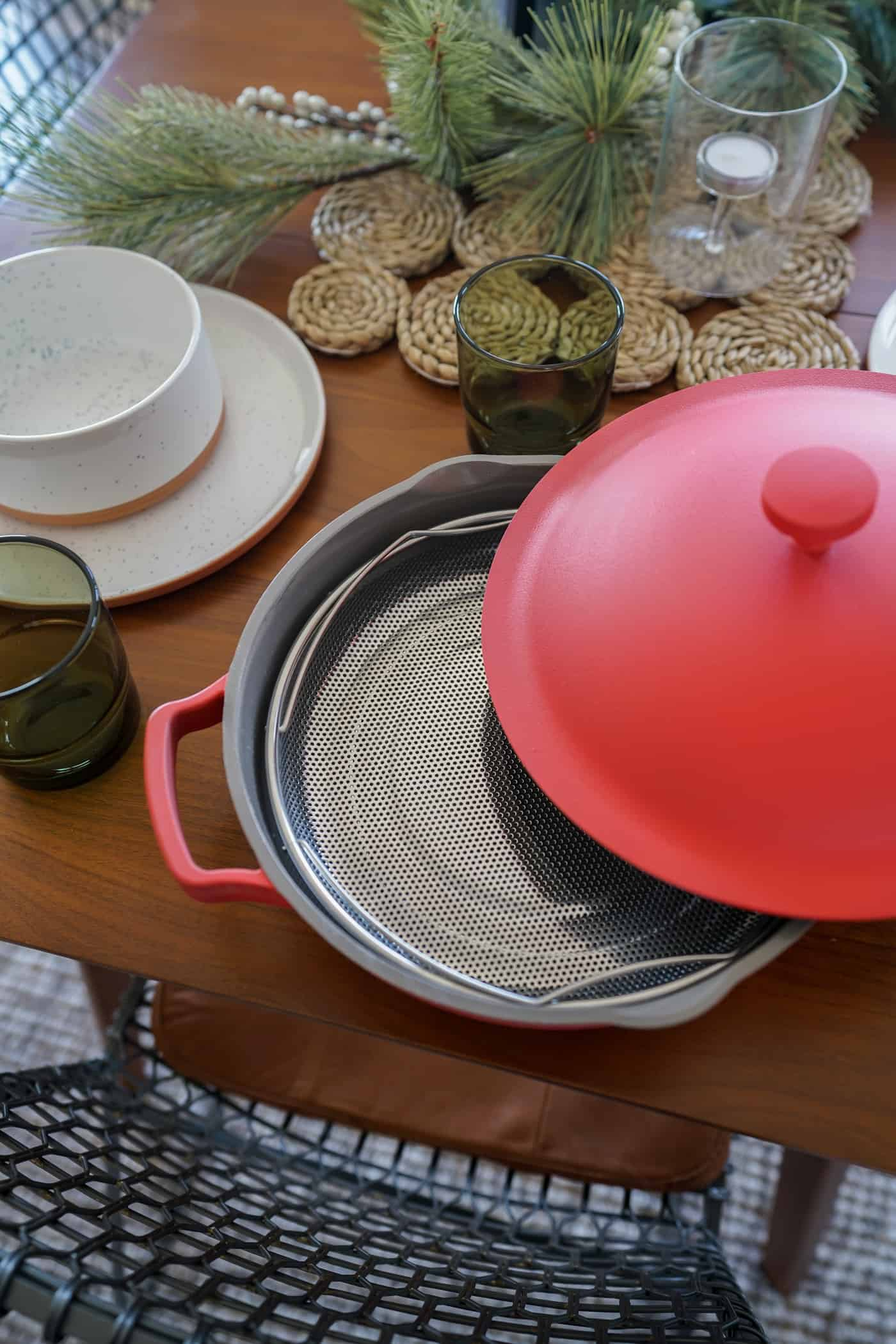 A brown dining room table with the Always Pan in color heat along with Our Place dishes