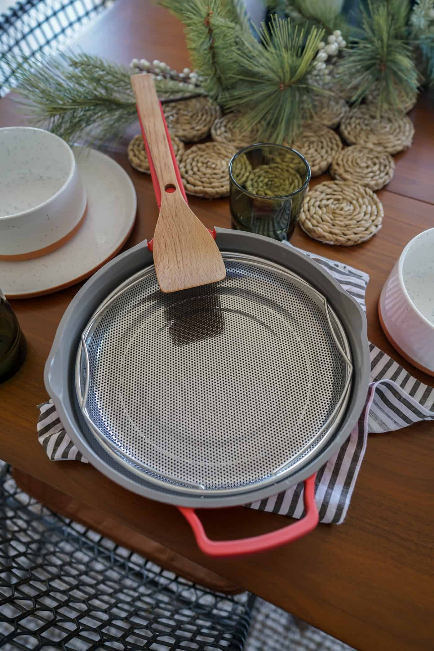 The Aways Pan by Our Place with steel colander and beechwood spoon placed on a dining room table