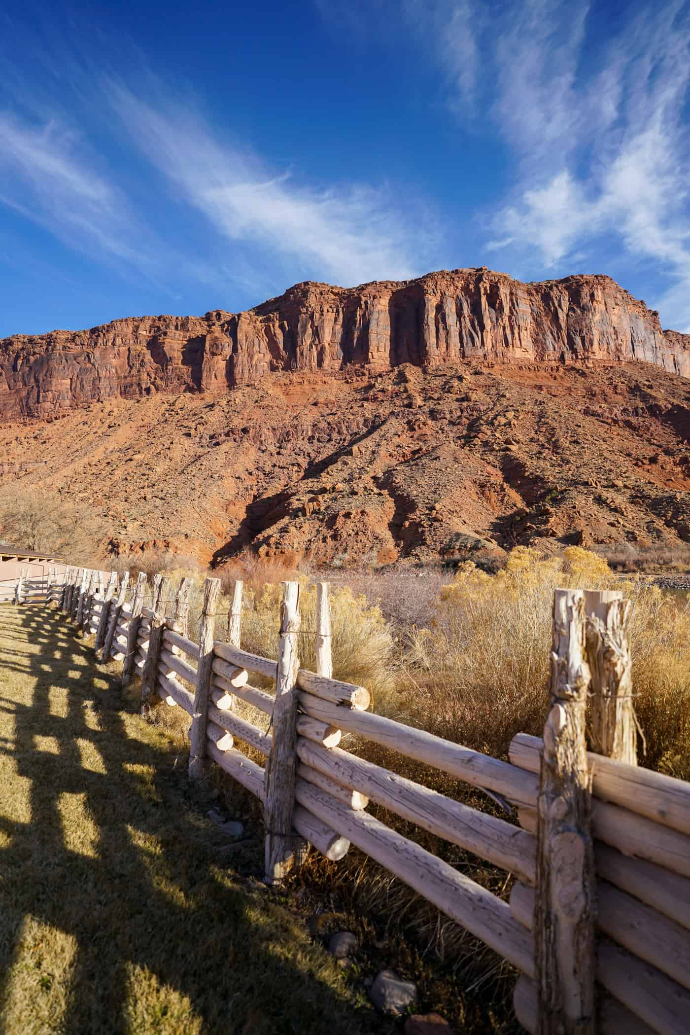 A wooden fence running along the Colorado River and red rocks of Moab Utah.