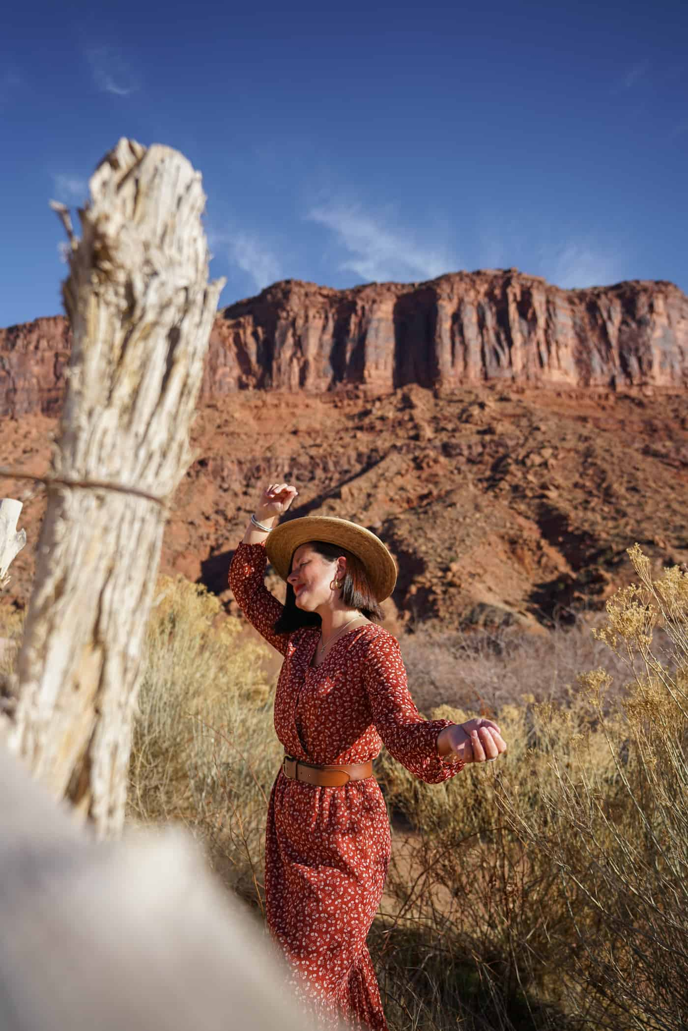 A women wearing a dress and a straw hat in the hills of Moab Utah.
