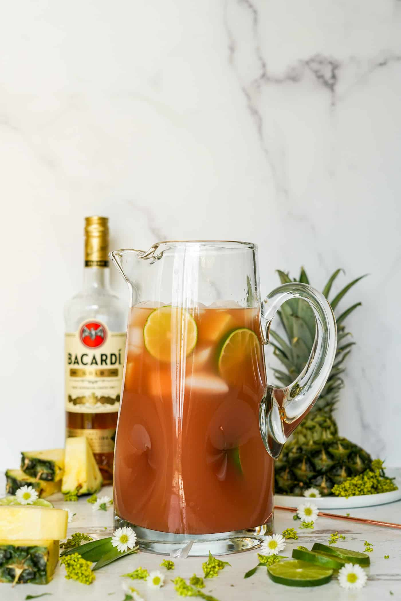 A large pitcher filled with bacardi rum punch recipe and fresh fruit chunks