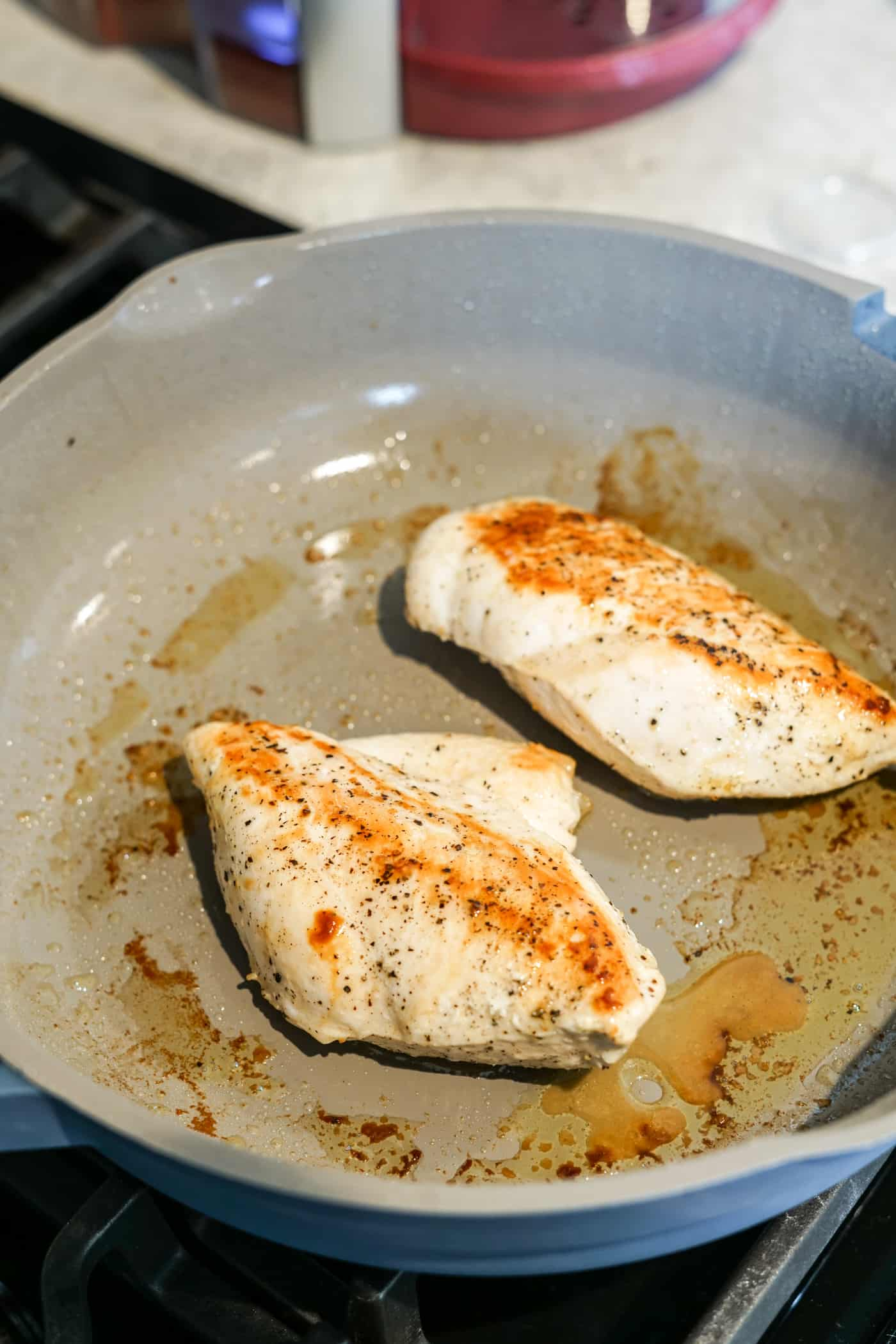 Two boneless chicken breasts in an our place always pan