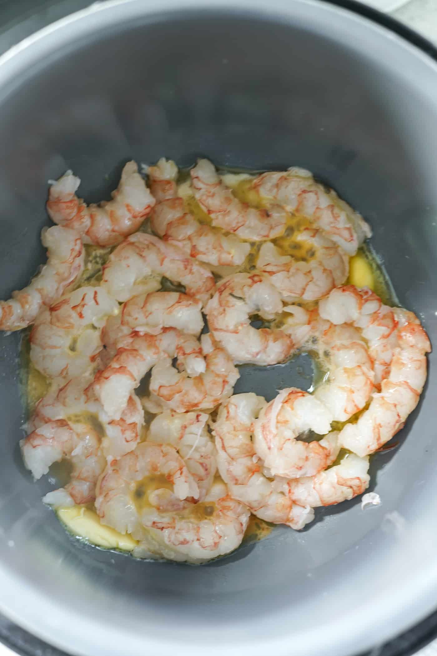 An Instant Pot filled with raw shrimp in butter and garlic