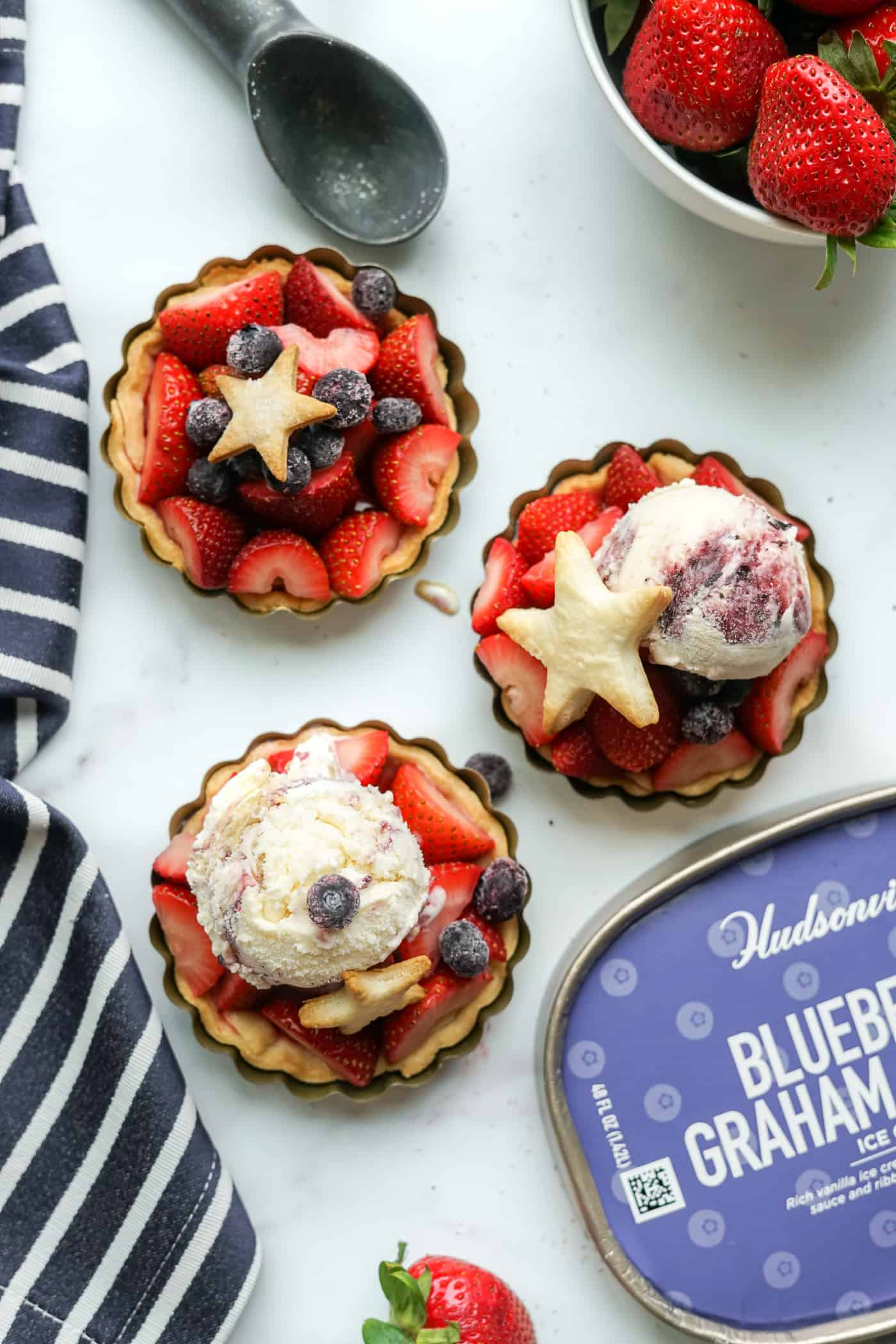 Three mini strawberry pies topped with a scoop of Hudsonville ice cream