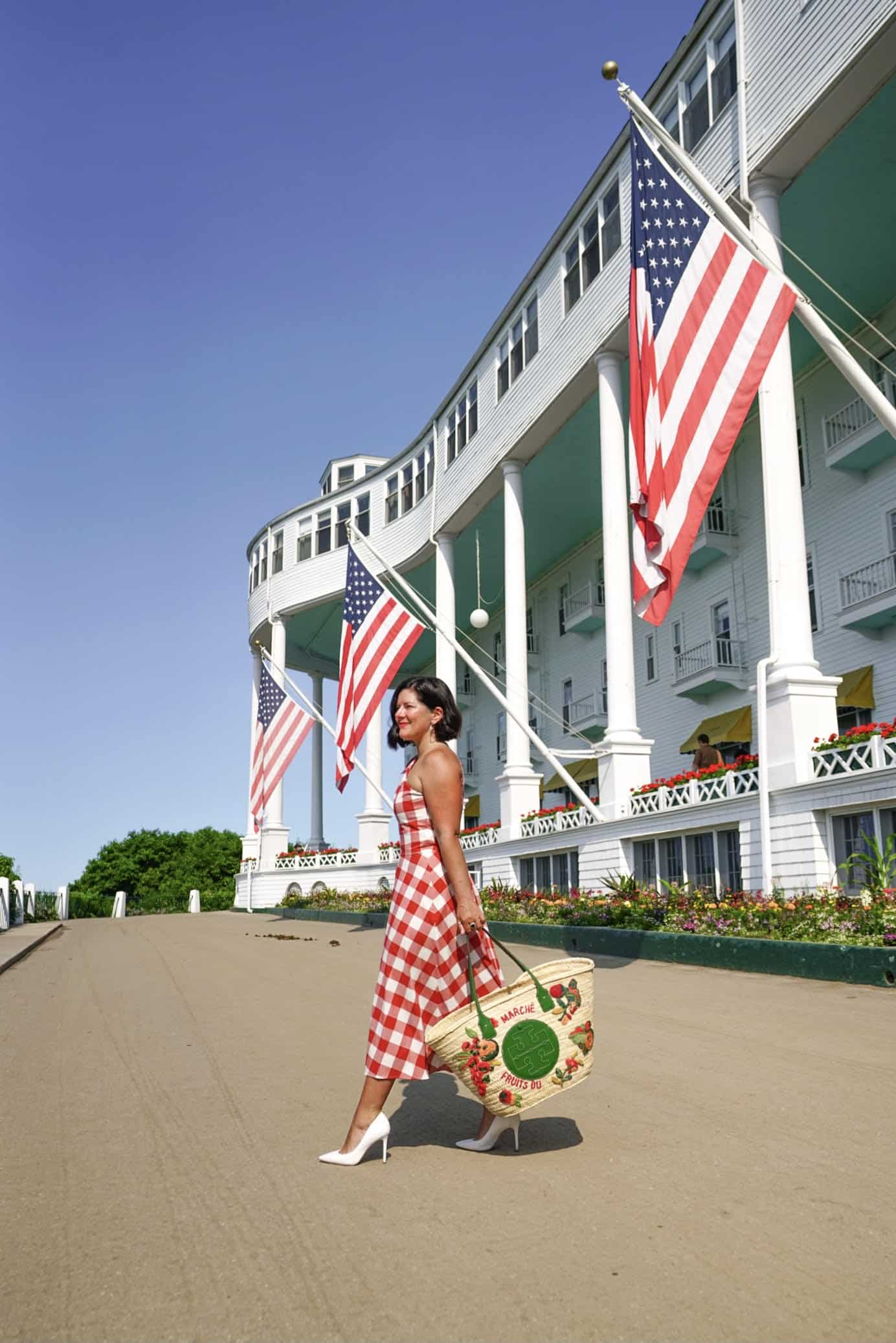 A women in the front of the Grand Hotel Mackinac Island with large American flags