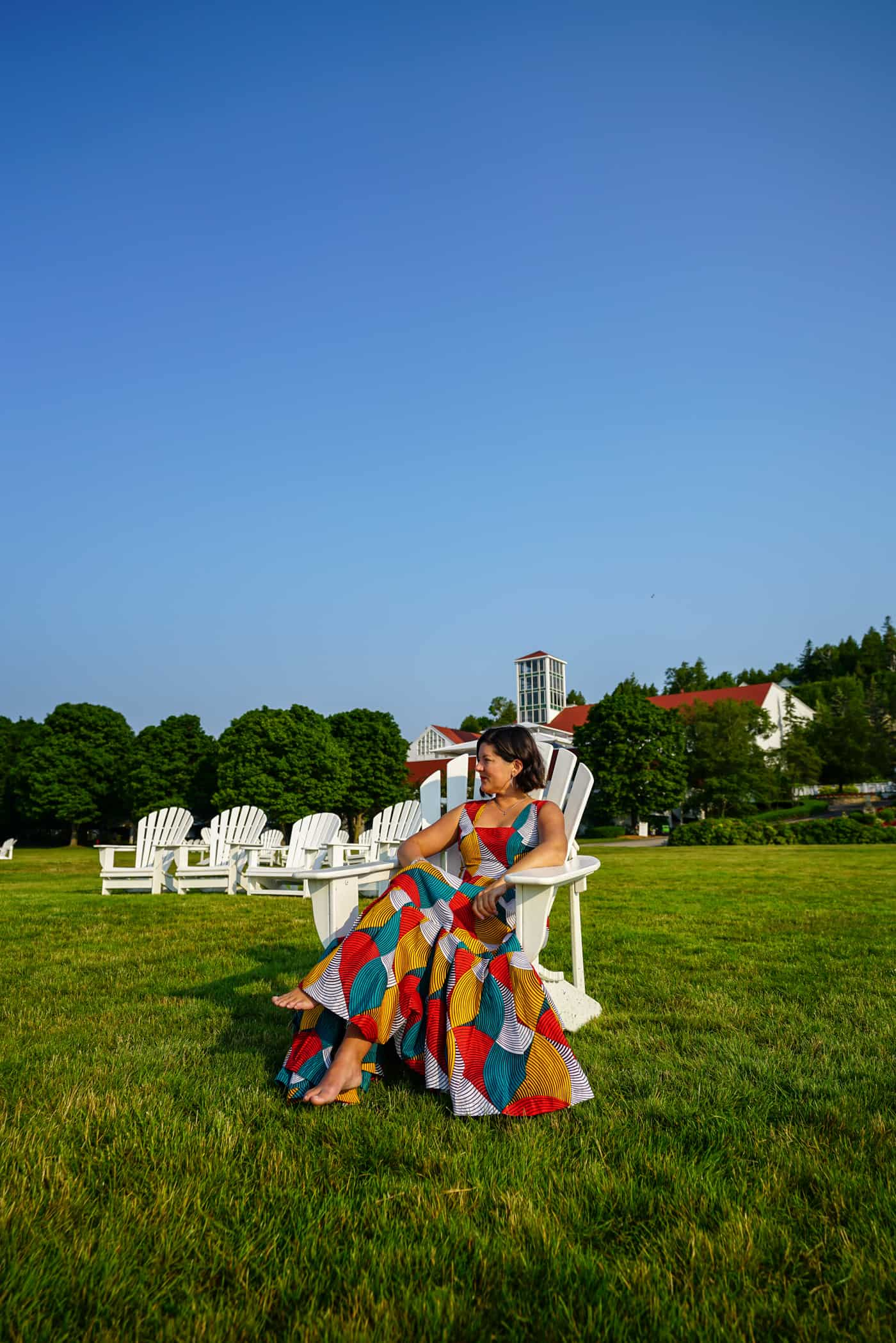 A women in a dress in an adirondack chair on the lawn of Mission Point Resort