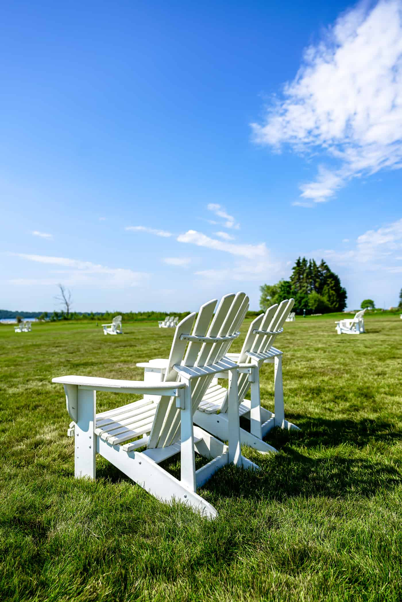 White adirondack charis on the lawn of Mission Point Resort