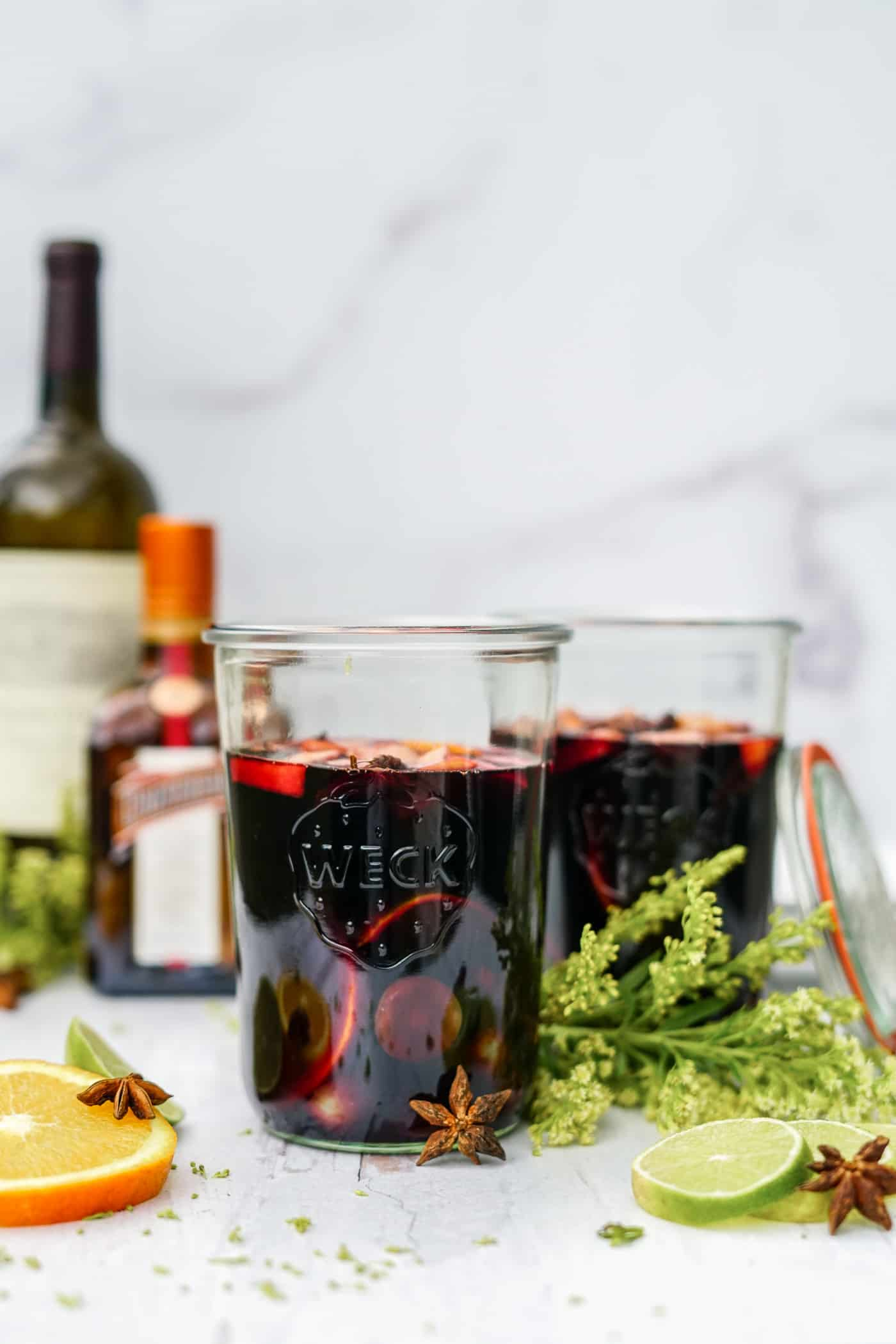 Two mason jars filled with red wine and fresh fruit.