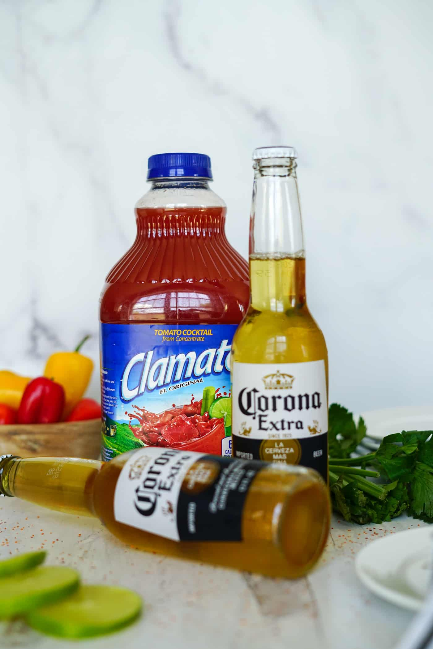 A large bottle of Clamato and two bottles of Corona beer for a Michelada recipe.