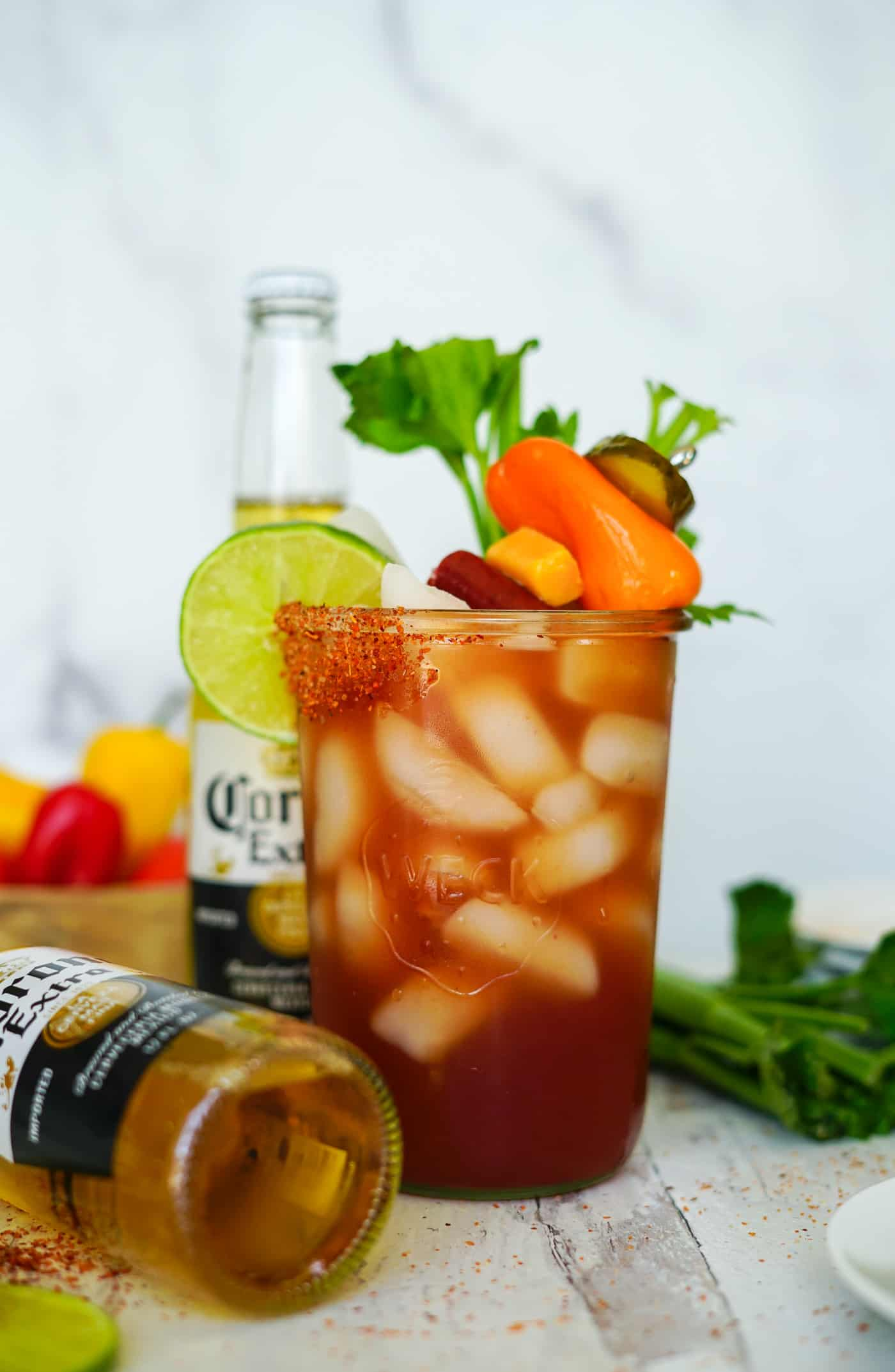 A large mason jar filled with a Michelada cocktail, lime wedge and celery stick