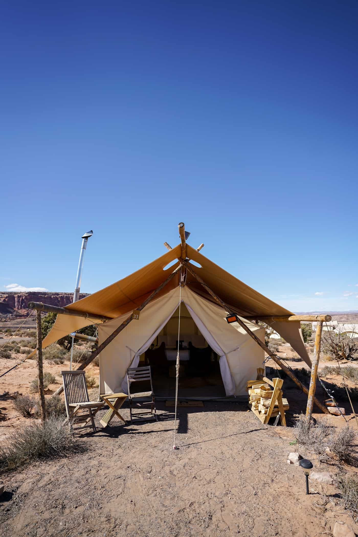 The outside of a large canvas tent for glamping in Moab at Under Canvas Moab