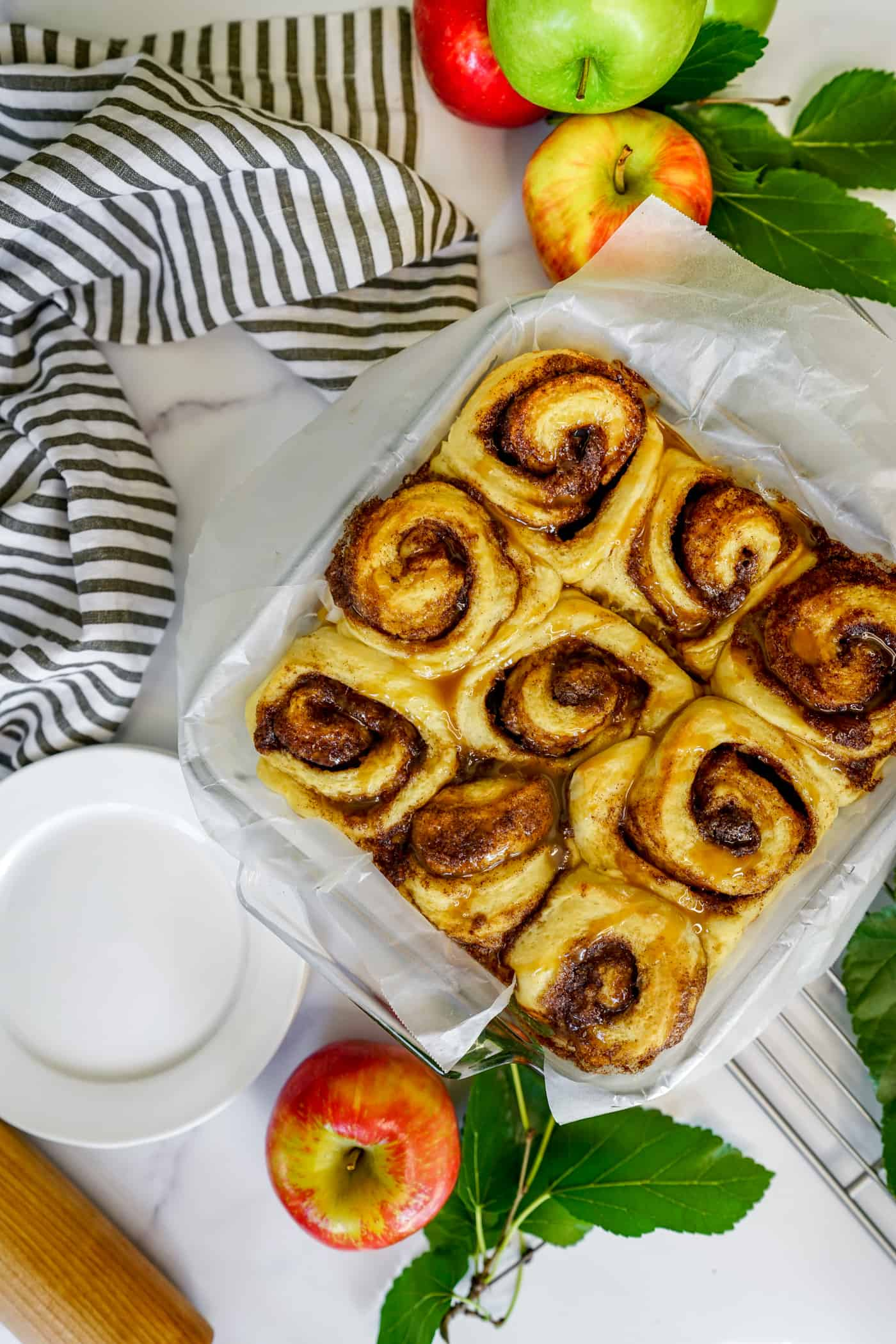A 9x9 glass baking dish filled with baked caramel apple cinnamon rolls.