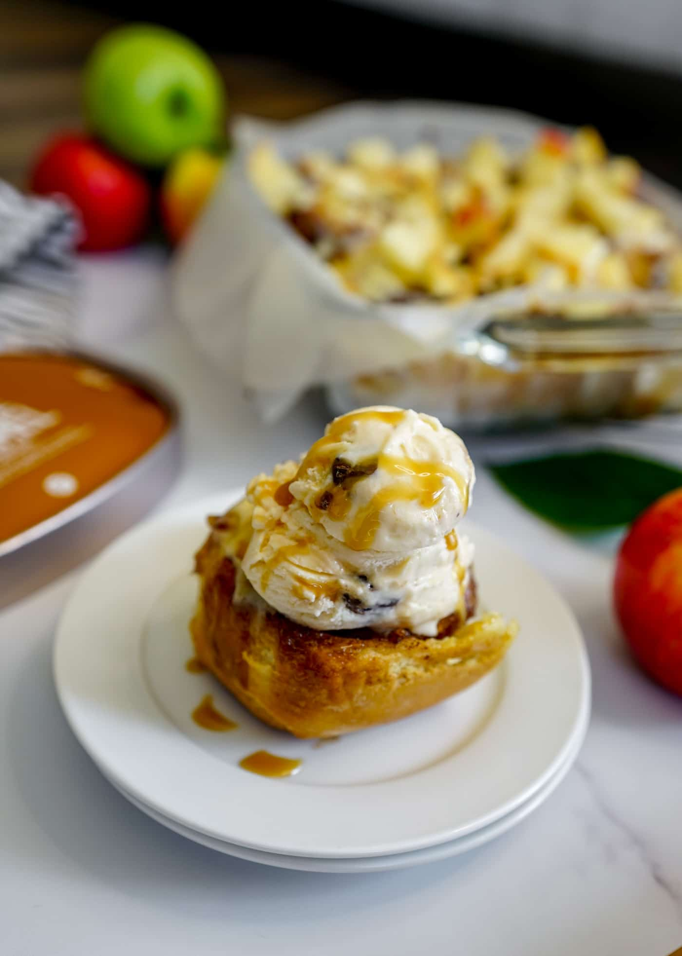 One warm caramel apple cinnamon roll topped with a scoop of Hudsonville Seaside Caramel ice cream.