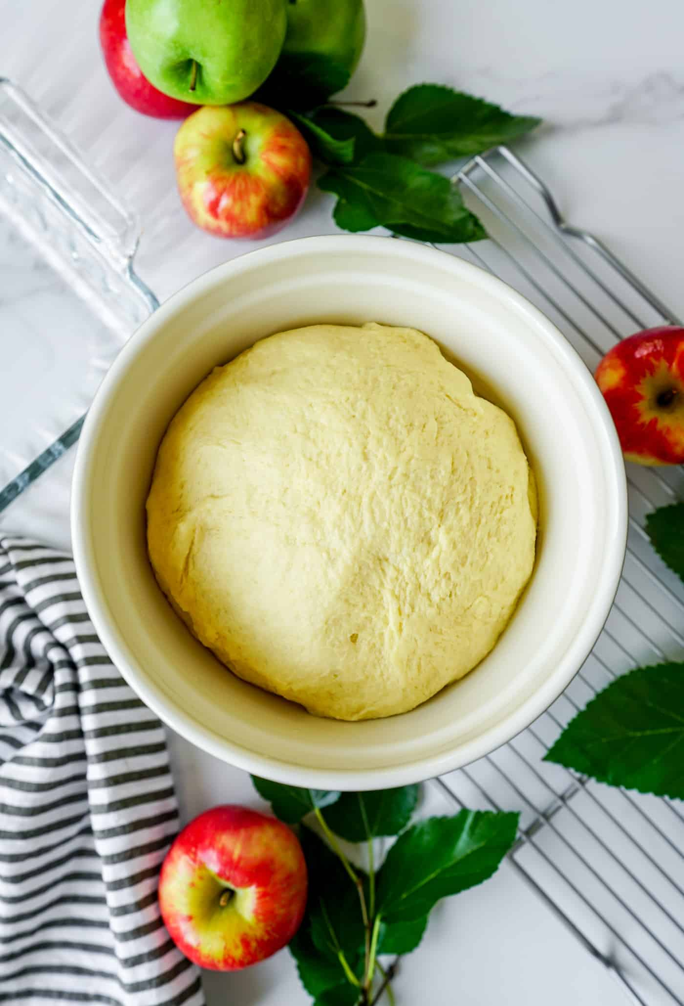 A large mixing bowl filled with homemade dough which has risen for homemade cinnamon rolls.