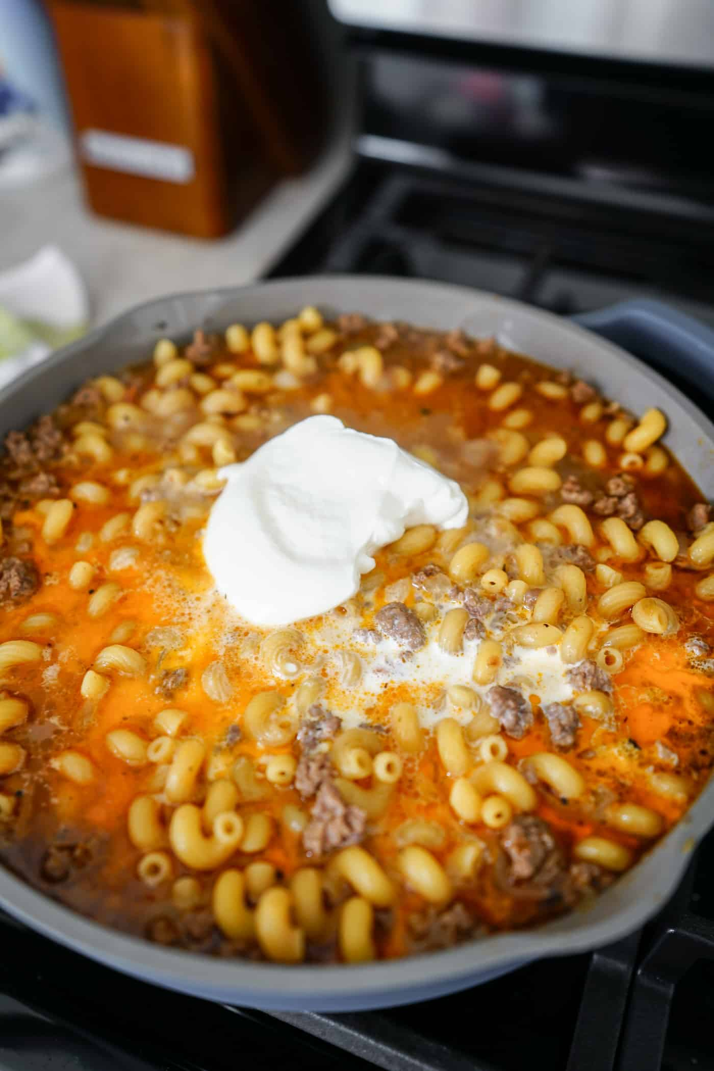 Pasta shells, ground beef, beef broth, cheese and sour cream cooking on the stove top in a large pan.
