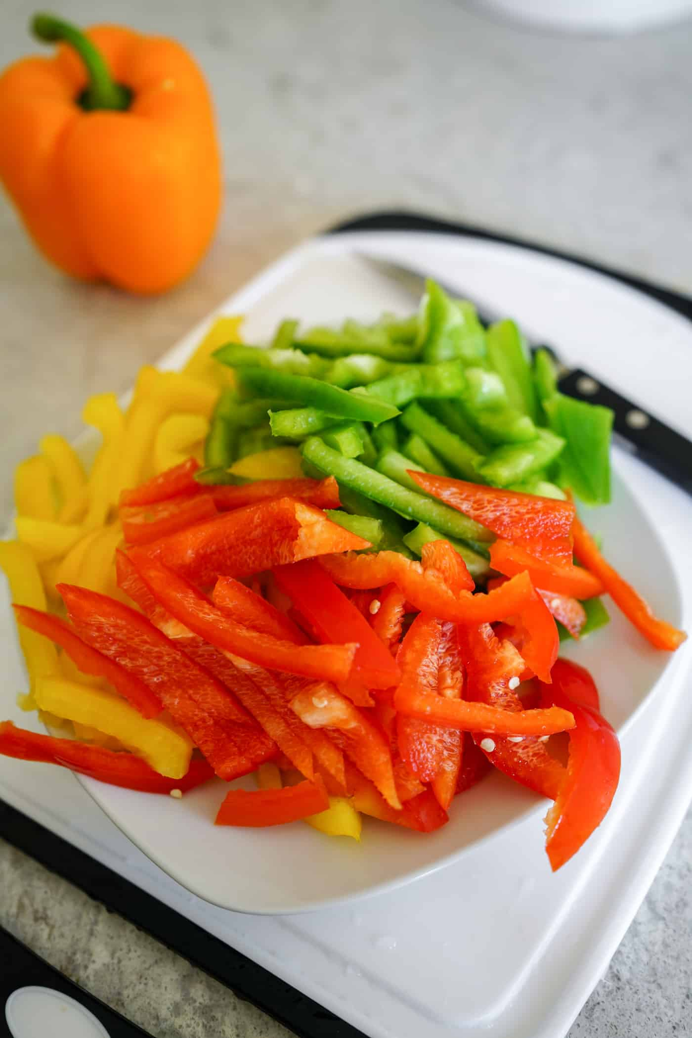 A plate filled with chopped red, green and yellow bell peppers for Instant Pot Chicken Fajita Pasta recipe.