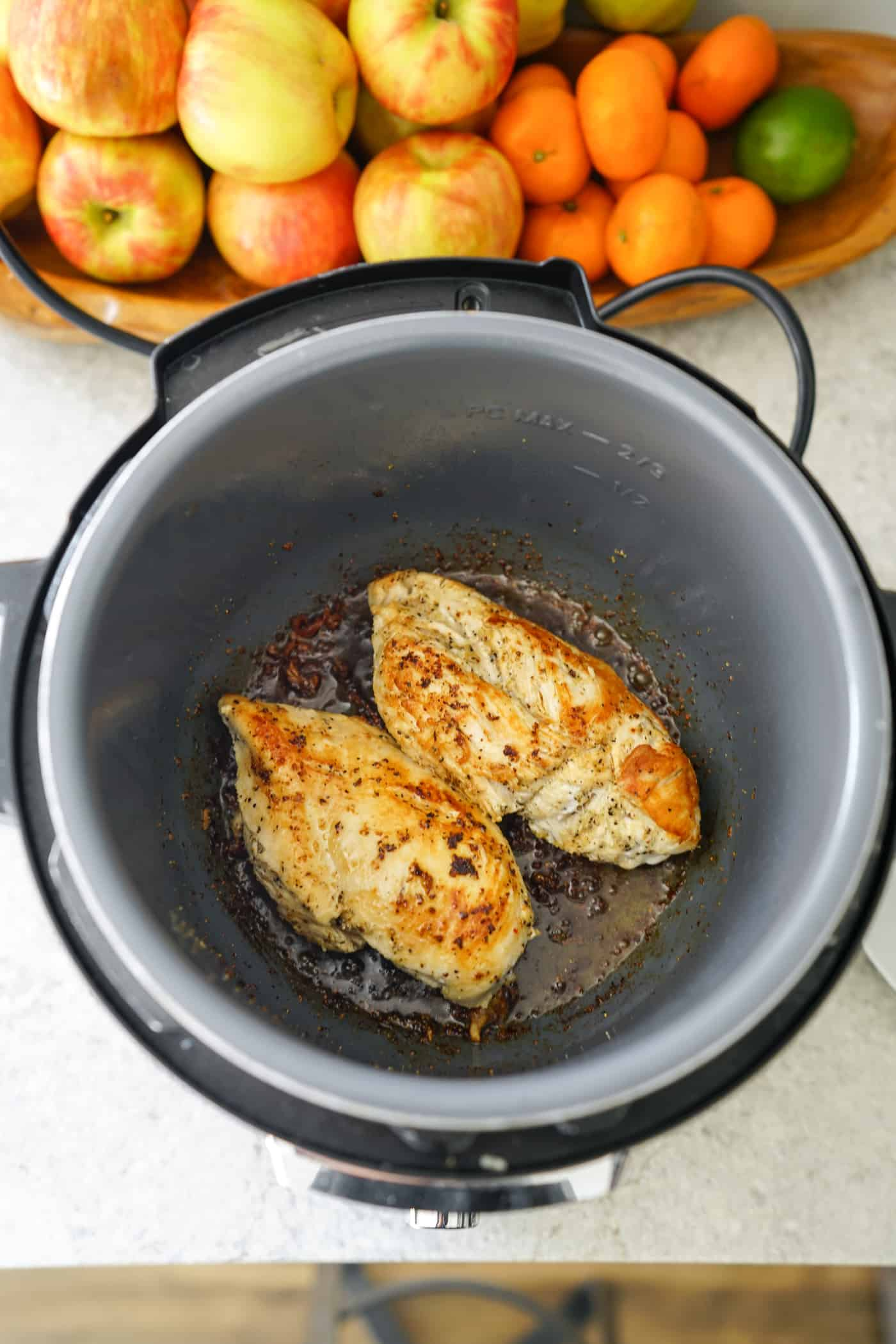 An Instant Pot with two boneless chicken breasts on the saute mode.