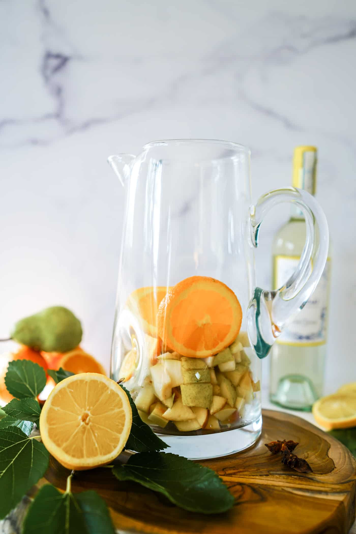 A large glass pitcher filled with orange slices and apple chunks for apple cider sangria.