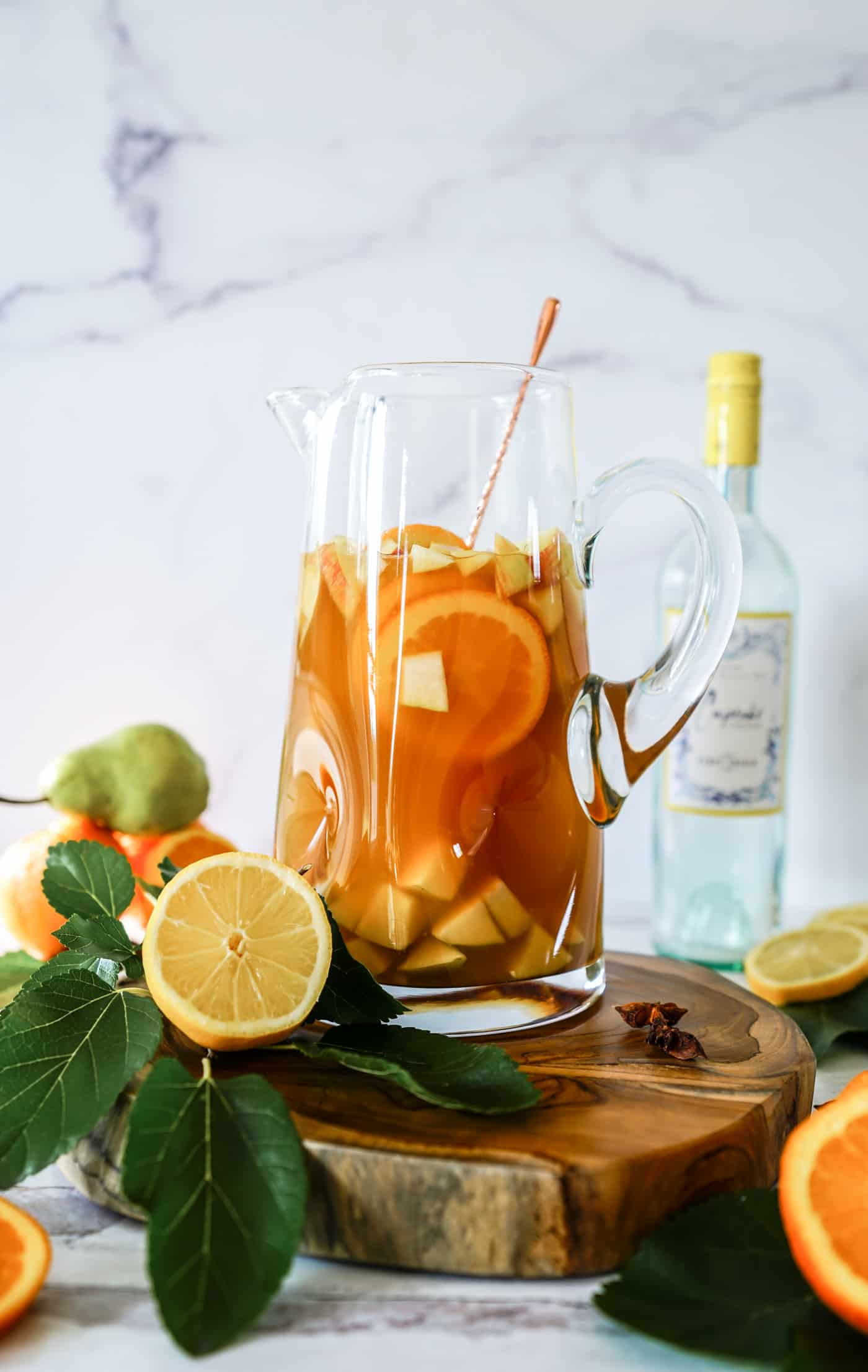 A large glass pitcher filled with Thanksgiving sangria recipe and fresh fruit chunks.